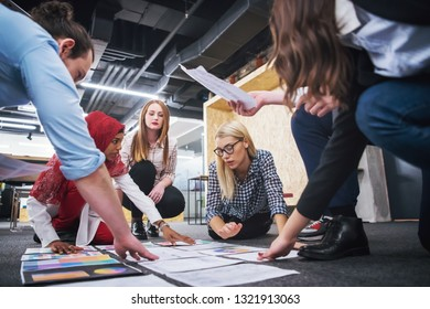 young blonde businesswoman having meeting with her multiethnic startup business team in modern office interior,presenting new ideas on the floor