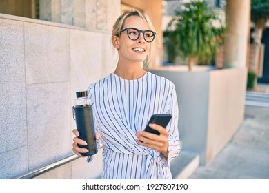 Young blonde businesswoman smiling happy using smartphone and drinking bottle of water at the city.