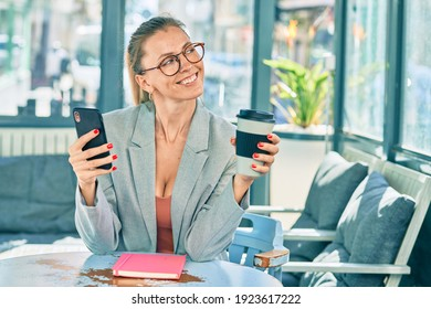 Young blonde businesswoman using smartphone and drinking coffee at the coffee shop.
