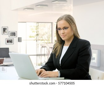 Young blonde caucasian business secretary working on laptop computer at home, sitting in front of desk, looking at screen, typing, wearing glasses.