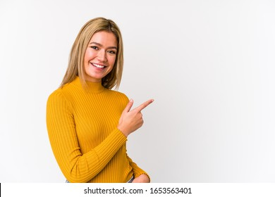 Young blonde caucasian woman isolated smiling and pointing aside, showing something at blank space.