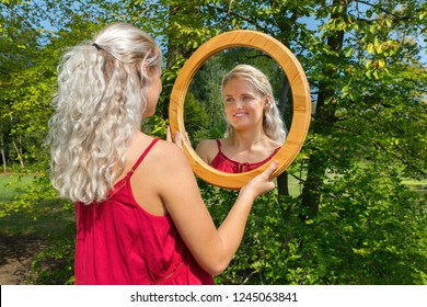 Young blonde caucasian woman looking in round wooden mirror outside