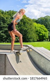 Young blonde caucasian woman on skateboard in halfpipe
