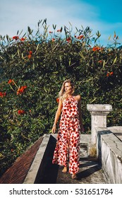 Young blonde caucasian woman posing in jumpsuit with red poppies for fashion portrait outdoor in Bali