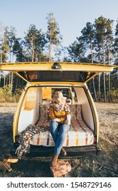 Young blonde Caucasian woman relaxing in yellow camper van during sunset. Vertical orientation