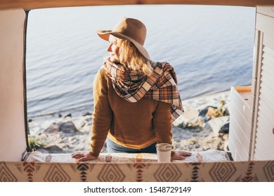 Young blonde Caucasian woman relaxing in her camper van during sunset at seaside