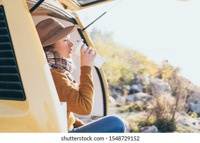 Young blonde Caucasian woman relaxing in yellow camper van during sunset