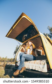 Young blonde Caucasian woman relaxing in yellow van during sunset. Vertical orientation