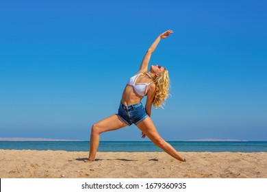 Young blonde caucasian woman training yoga on  beach near sea