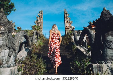 Young blonde caucasian woman traveling in the mountains, north of Bali, luxury vacation, explore and discover the world, Balinese gates