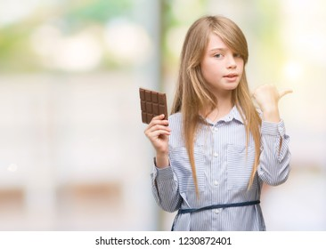 Young blonde child holding chocolate bar pointing with hand and finger up with happy face smiling