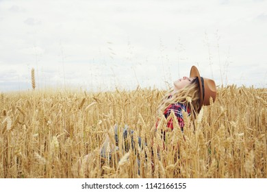 Young and blonde country woman possing in a field of wheat in a summer day