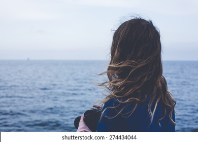 young blonde curly girl looking at hazy sunshine through a thick mist on a calm sea and blue skies back view