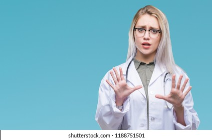 Young blonde doctor woman over isolated background afraid and terrified with fear expression stop gesture with hands, shouting in shock. Panic concept.