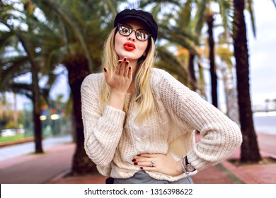 Young blonde elegant stylish woman sending kiss and posing on Barcelona street with palm trees, wearing cozy sweater, cap and clear glasses, fashion style, travel mood, spring time.