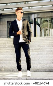 Young blonde fashion man looking to one side in white shirt, black suit and white sneakers against grey stairs. Good looking business man with black sunglasses and short blond hair. Tough guy