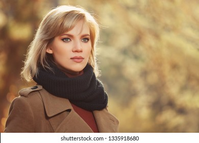 Young blonde fashion woman walking in autumn park Stylish female model wearing classic beige coat and black scarf