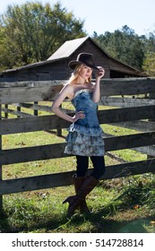 Young Blonde Female In Black Hat Standing Next to Farm Fence