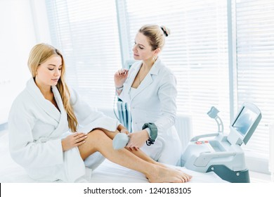 Young blonde female client chooses laser hair removal cosmetology procedure instead of waxing, talking with a therapist at cosmetic beauty spa clinic. Laser epilation and cosmetology.