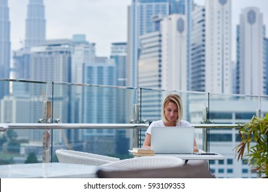 Young blonde female freelancer making distance job project for web design agency working on free schedule during leisure on weekends while sitting in rooftop terrace cafe using laptop and wifi