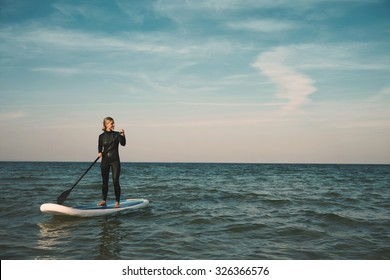 Young blonde female paddles a paddleboard at the sea