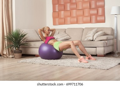 young blonde female in sportswear doing exercise for abs on fit-ball indoor at home