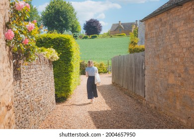 A young blonde female tourist explores a quaint country lane in the rural English countryside village of Chipping Campde, on a summer day in the Cotswolds, Gloucestershire, UK.