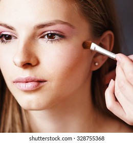 Young blonde girl applying make-up by make-up artist in studio,