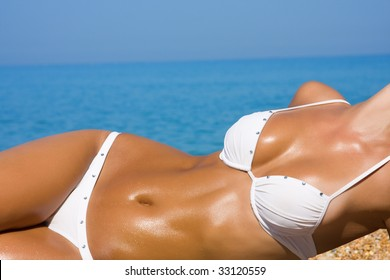 The young blonde girl with a beautiful body sunbathes on a beach in a white bathing suit against the sea