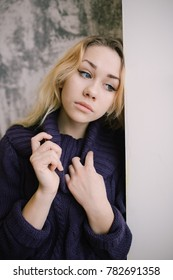 young blonde girl with big sad eyes standing near the window. emotional portrait. dressed in a warm winter sweater. costs about textured walls