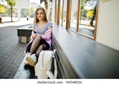 Young blonde girl in black skirt and pink coat with woman backpack sitting on bench at city.
