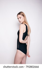 young blonde girl with clean skin and athletic figure is dressed in bodysuit posing in Studio on a white background. emotional portrait. examples of posing for model test. big eyes and long hair