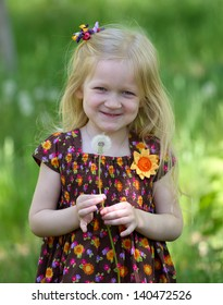young blonde girl with dandelion on a green lawn