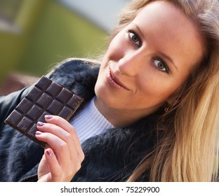 Young blonde girl eating a chocolate