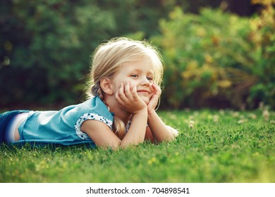 Young blonde girl is enjoying grass in the morning.