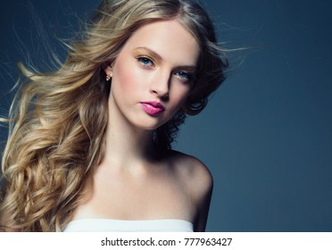 Young blonde girl female with long curly blonde hair and pink lipstick on lips, healthy  hair and makeup.Young beauty