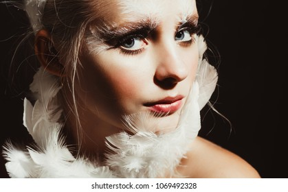 A young blonde girl with good sking and nude make up posing for the beauty photography shooting, image of a bird, white swan, feather accessories