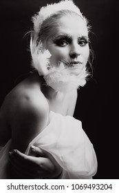 A young blonde girl with good sking and nude make up posing for the beauty photography shooting, image of a bird, white swan, feather accessories, black and white image