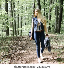 Young blonde girl hipster forest hike with a backpack in jeans