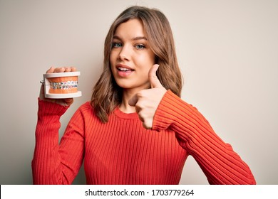 Young blonde girl holding orthodontist prosthesis denture over isolated background happy with big smile doing ok sign, thumb up with fingers, excellent sign