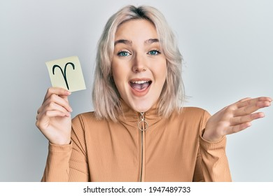 Young blonde girl holding paper with aries zodiac sign celebrating achievement with happy smile and winner expression with raised hand