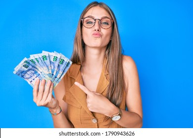Young blonde girl holding south african rand banknotes looking at the camera blowing a kiss being lovely and sexy. love expression.