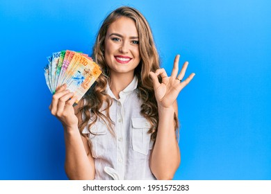 Young blonde girl holding swiss franc banknotes doing ok sign with fingers, smiling friendly gesturing excellent symbol