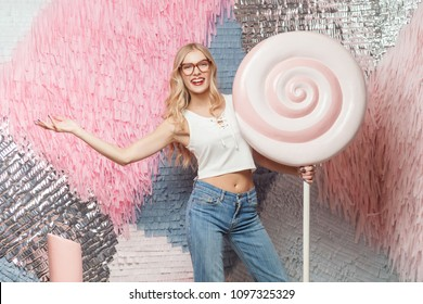 Young blonde girl with long hair in stylish red glasses holdings in hand huge lollipop, having funny look on colorful abstract background, studio shot