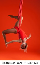 A young blonde girl with long hair in a red suit performs gymnastic and exercises on silk. Studio shooting on orange background