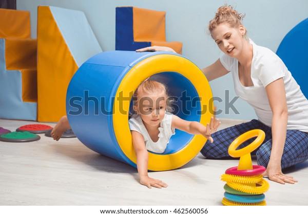 Junge blonde Mädchen, die auf der zylindrischen Matratze liegt