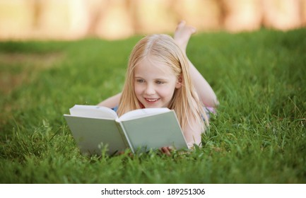 A young blonde girl is lying on the green grass outdoors reading a white book in summer
