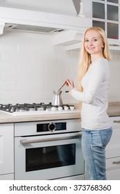 young blonde girl make coffee in turk