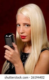 Young blonde girl with the microphone in sexy pose