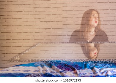 young blonde girl with a mirror, with half of the body erased on a brick background